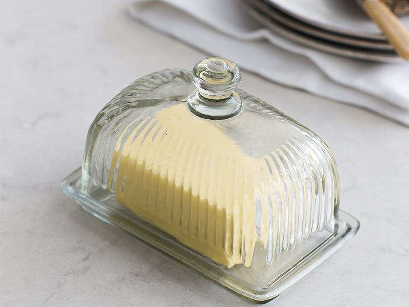 Butter in a vintage style glass butter dish on a marble kitchen counter