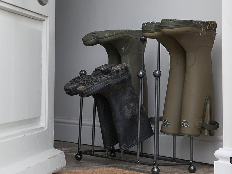 Two pairs of wellies upside down on Farringdon Welly stand in the hallway, next to an open back door.