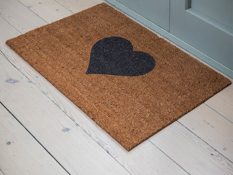 Heart Coir Doormat on a light grey wooden floor in front of a blue door