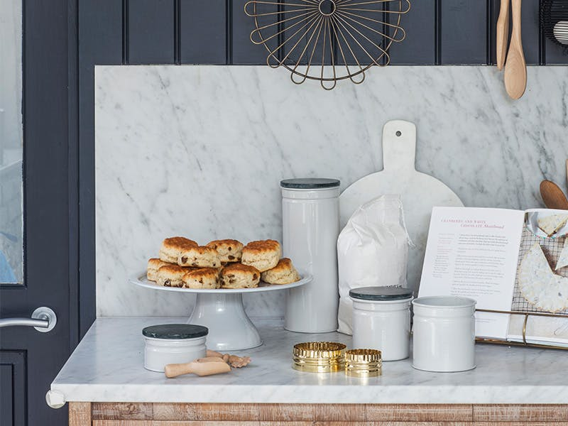 Baking accessories on a marble counter top with a cake stand full of fruit scones