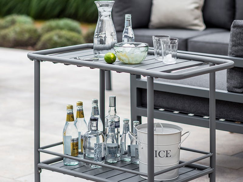 Drinks Trolley laid with glassware, drinks, bottles and lime on an outdoor patio