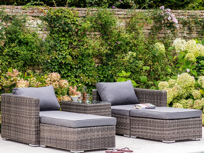 Selborne Double Lounger Set set against a foliage-covered costwold stone wall