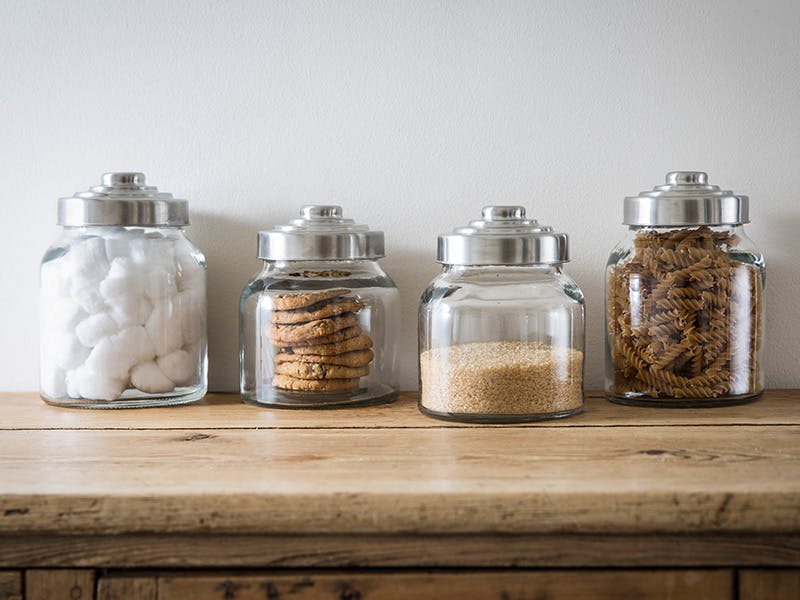 Collection of Glass Jars filled with cotton wool, cookies, brown sugar and fussili pasta