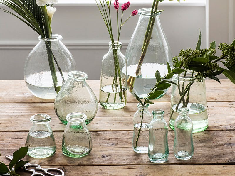 Recycled glass vases on tabletop with assorted stems