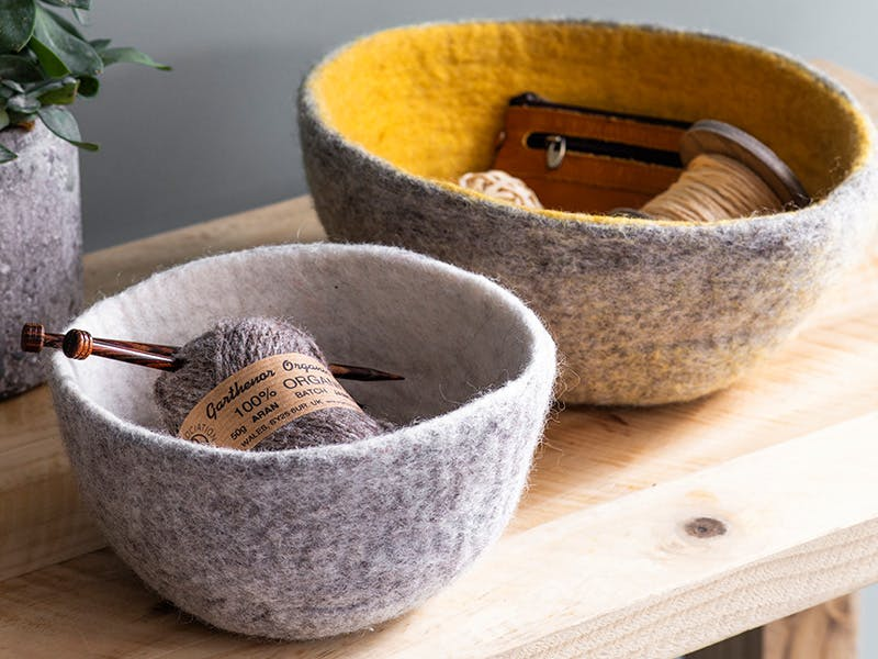 Faitrade Southwold Felt Bowls containing wooden knitting needles, wool and string
