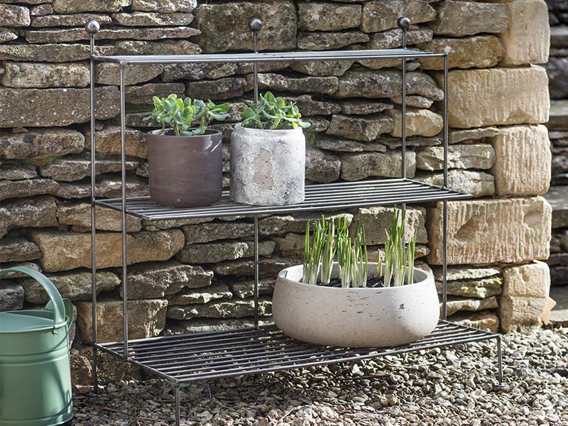 Barrington Plant Stand holding mulitple plant pots set against a cotswold stone wall