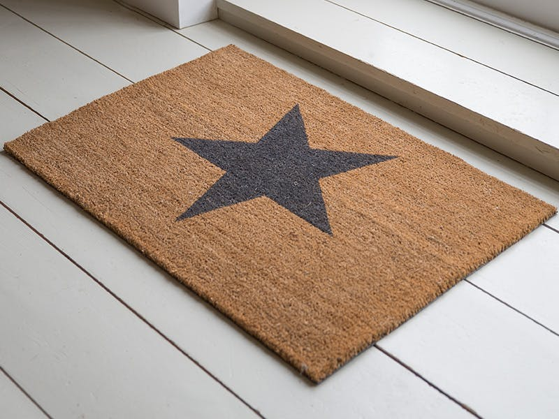 Star Doormat on white wooden floor