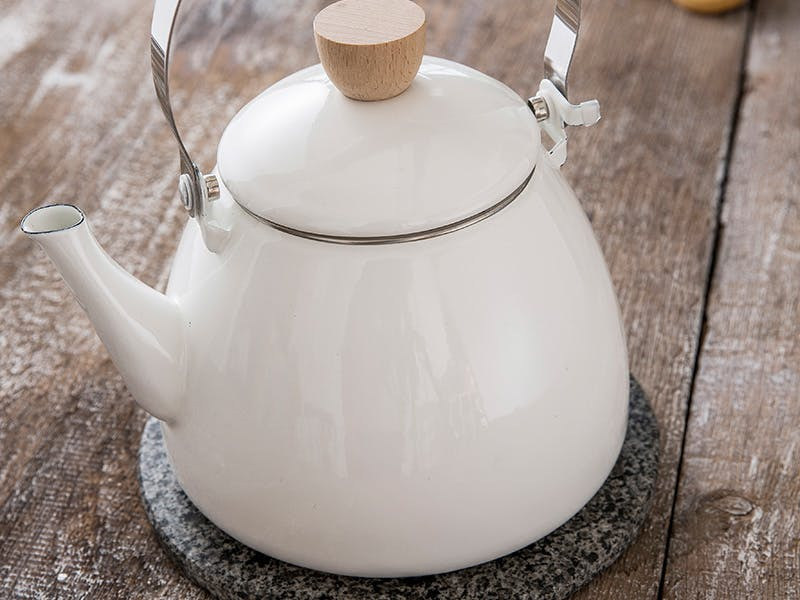 Warm White Stove Kettle on Wooden Surface