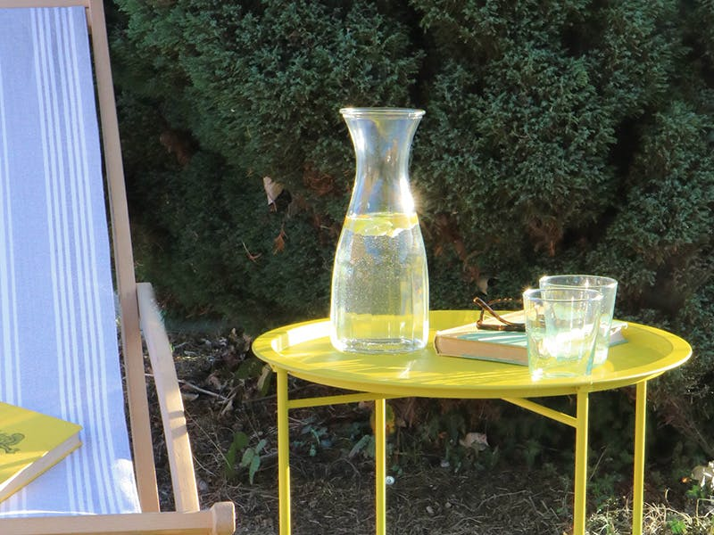 Rive Droite Outdoor Bistro Tray Table in Dandelion. Laid with a drinks carafe, glasses, book and sunglasses and next to a deckchair