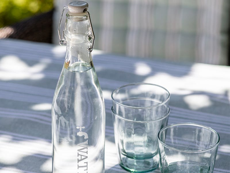 Water Tap Bottle on an outdoor table with a set of reycled glass tumblers