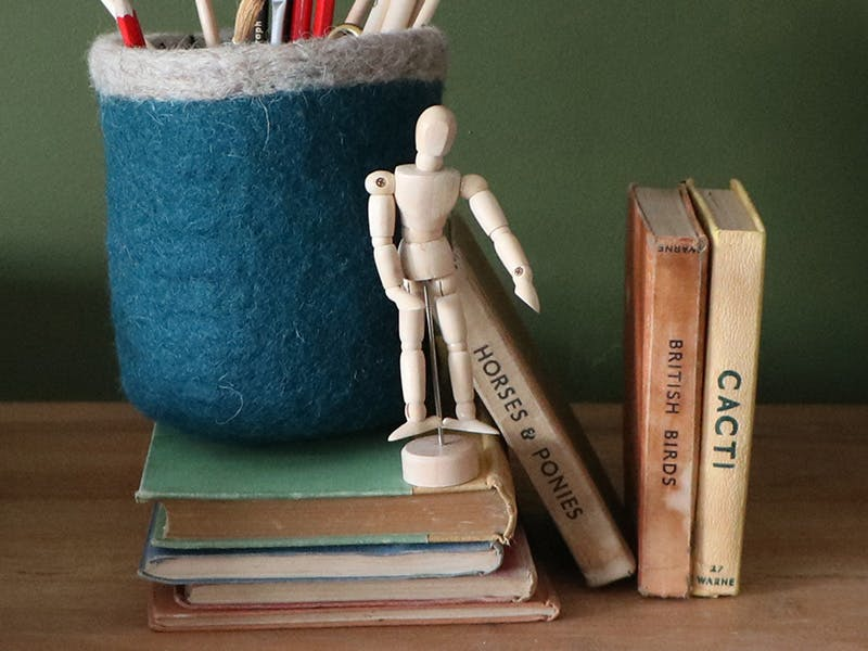 Pencils in a blue felt pot with a moveable drawing figure, vintage books and writing pads