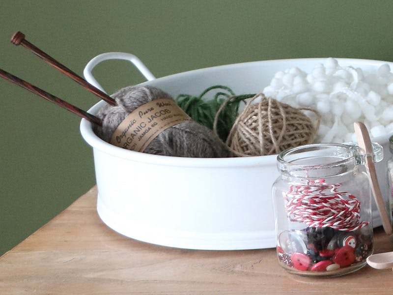 Natural knitting needles and wool in a white round tray with buttons and ribbons in two small jars