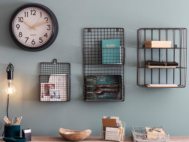 Home Office wall storage with magazine rack, letter holder and file storage set above desk and next to large Greenwich wall clock
