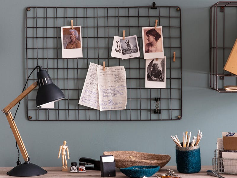 Farringdon wirework memo board with art postcards and to-do lists above a desk with storage pots and a lamp