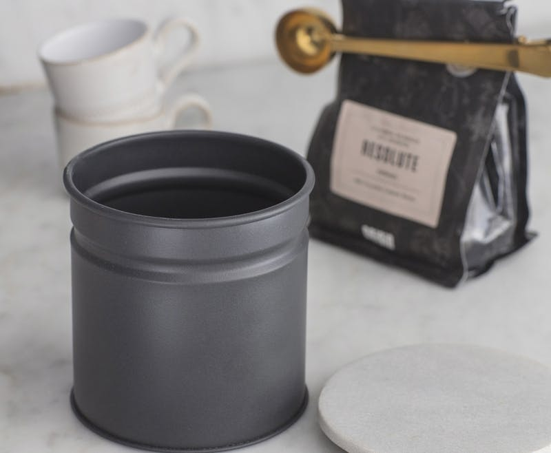 Open canister on the counter set next to coffee clipped with bass coffee scoop and two stacked white mugs