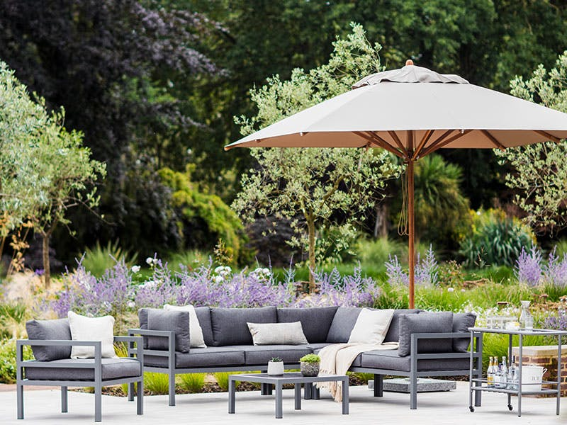 Parasol and sofa set by the pool in the sunshine