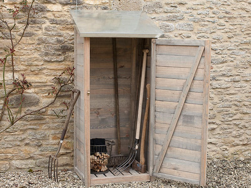 Narrow garden shed containing tools set against a cotswold stone wall