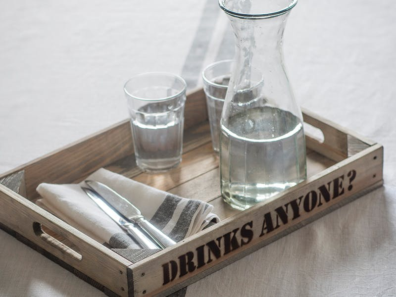 Rustic wooden tray laid with Glass carafe, tumblers and plates with napkins on top.