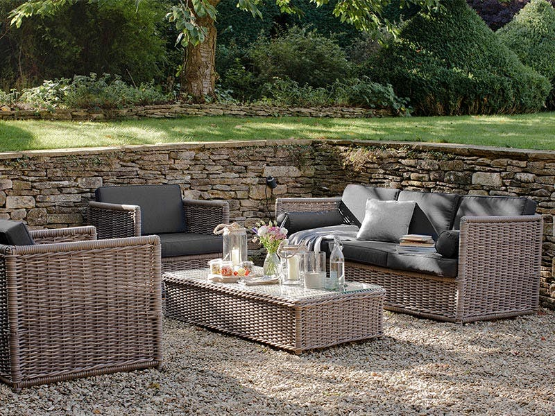 Rattan corner sofa set in the shade of the trees with glasses, candles and flowers laid on the table
